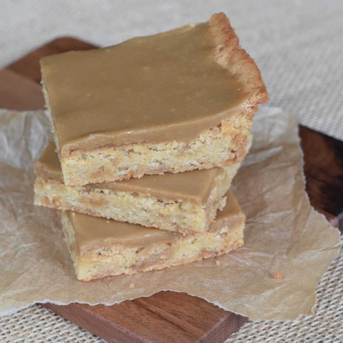stacked blonde brownies iced on wooden cutting board