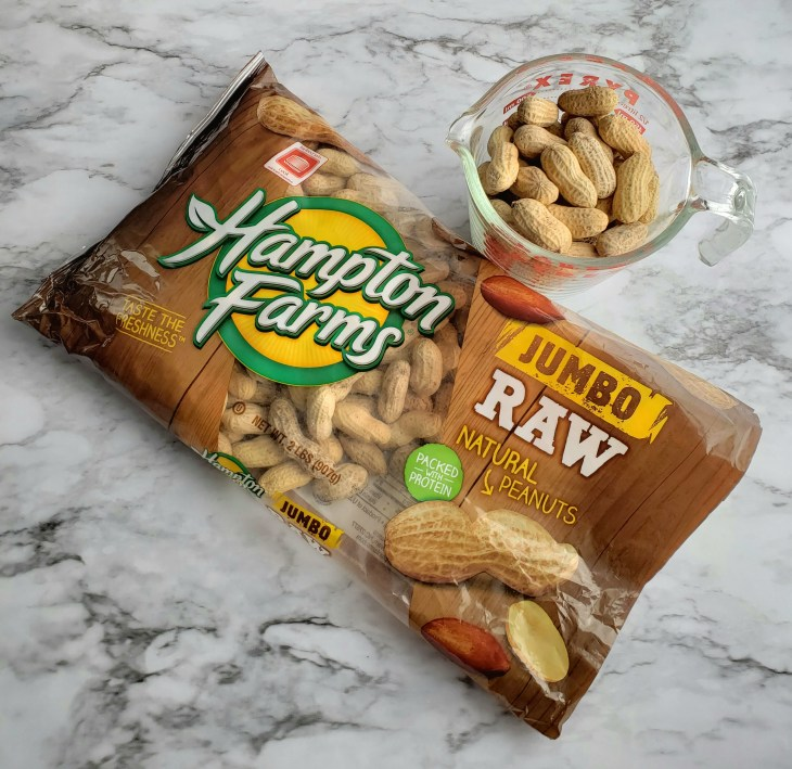 Hampton Farms raw peanuts in a bag with some in a glass bowl on a granite countertop
