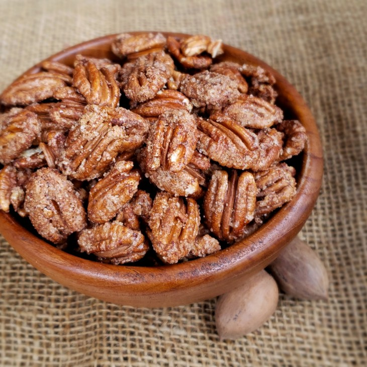 Cinnamon Sugar Pecans in a wooden bowl on burlap with two pecans in the shell
