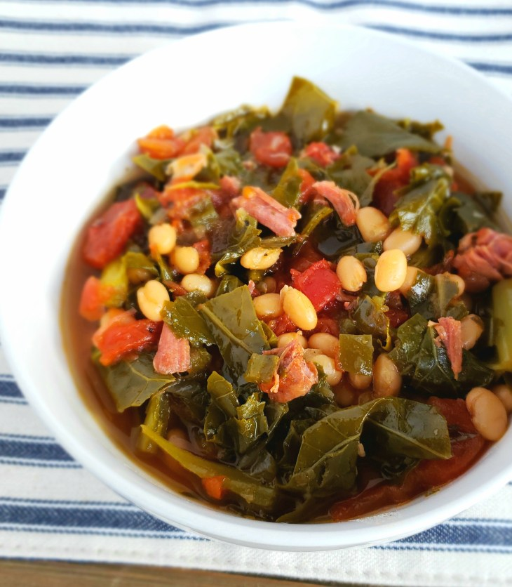 Collard Greens and Navy Beans are cooked in a fraction of the typical time when cooked in the Instant Pot. Served in a white bowl on a blue and white striped placemat