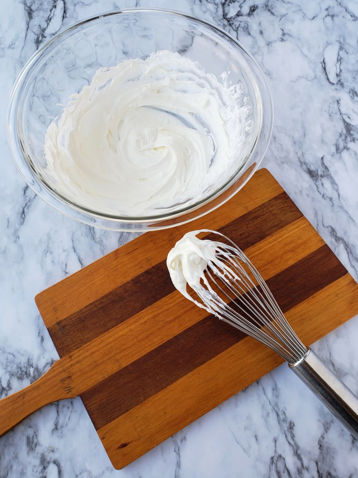 Neufchatel and sugar free Coo Whip stirred together with a wire whisk to create a creamy mixture to layer with sweet tea-soaked angel food cake cubes for Sweet Tea Tiramisu Trifle for two in a glass bowl
