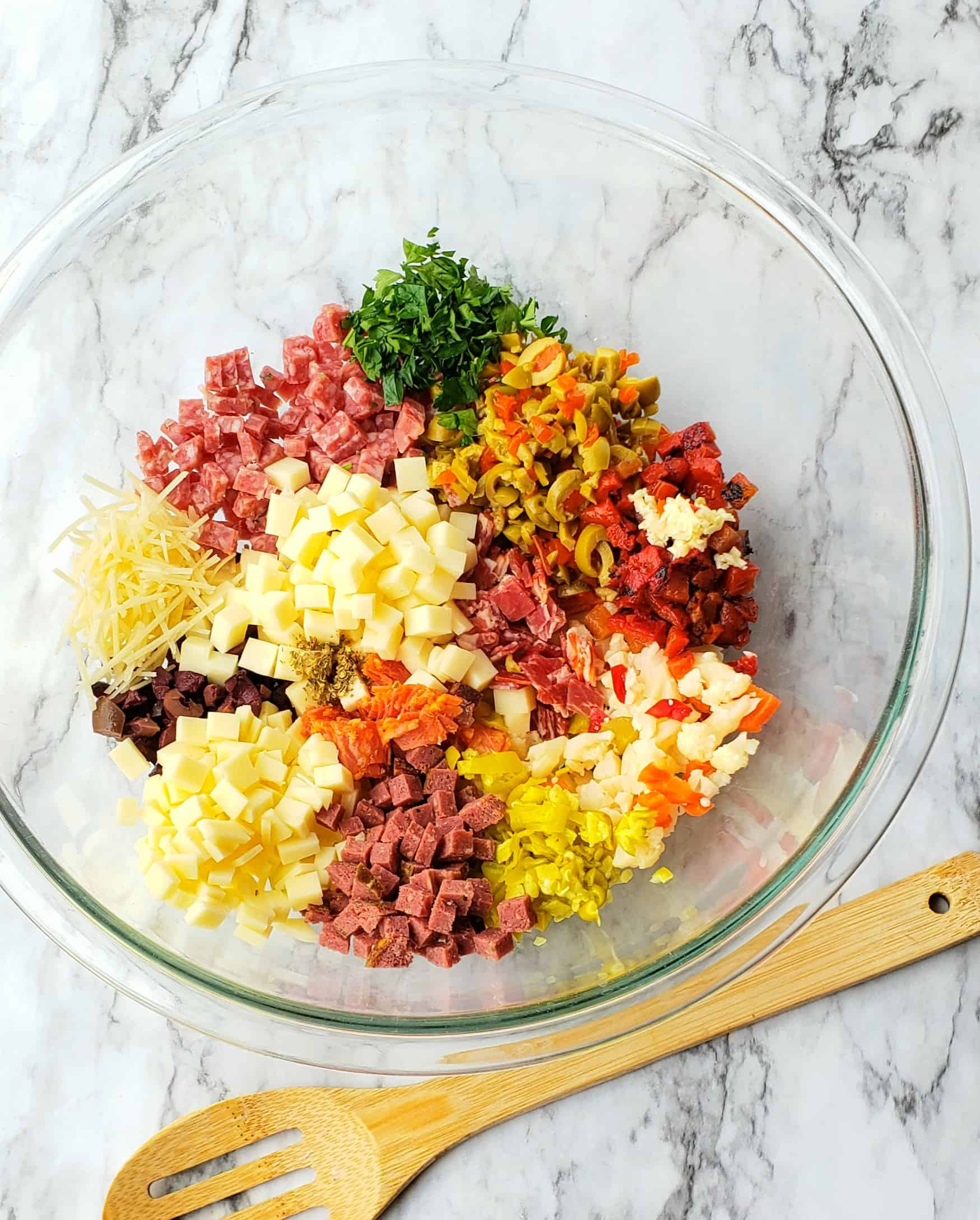 Finely chop the pickled veggies, olives, peppers. Mince the garlic and parsley. Dice the cheeses and meats.