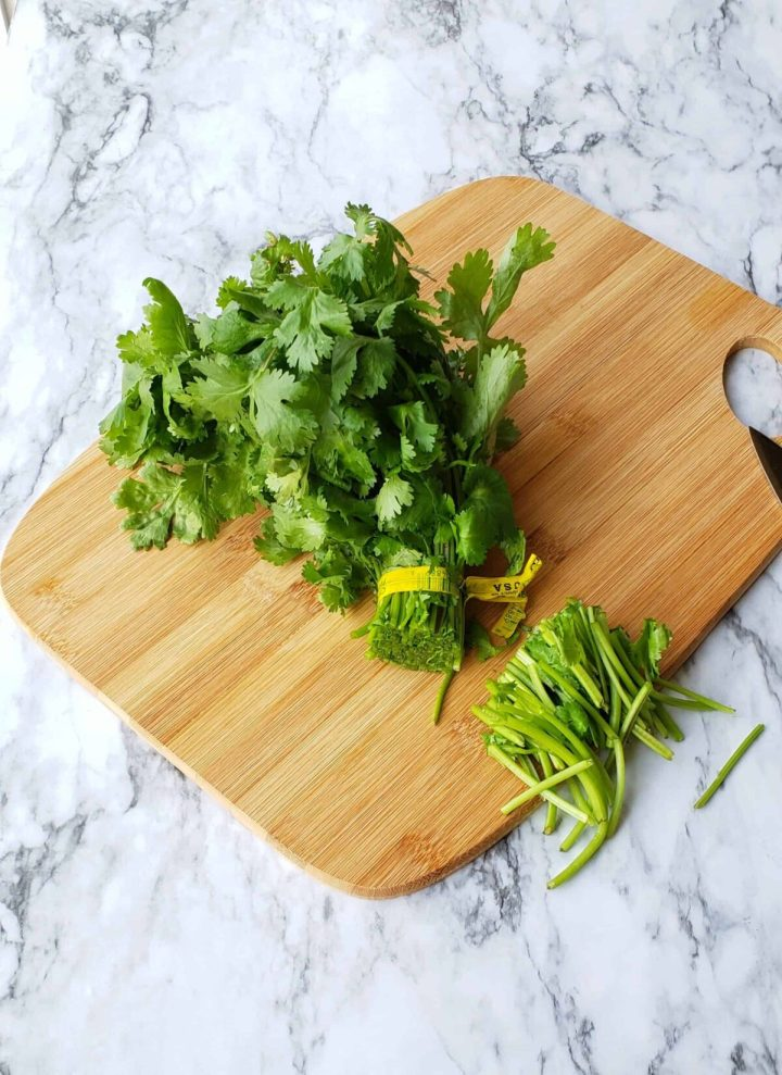 cut off cilantro stems from the plant. Wooden cutting board on marble surface