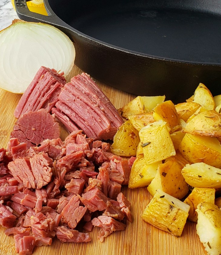 Corned Beef Hash is made with leftover corned beef brisket, potatoes, and an onion in a cast iron skillet.