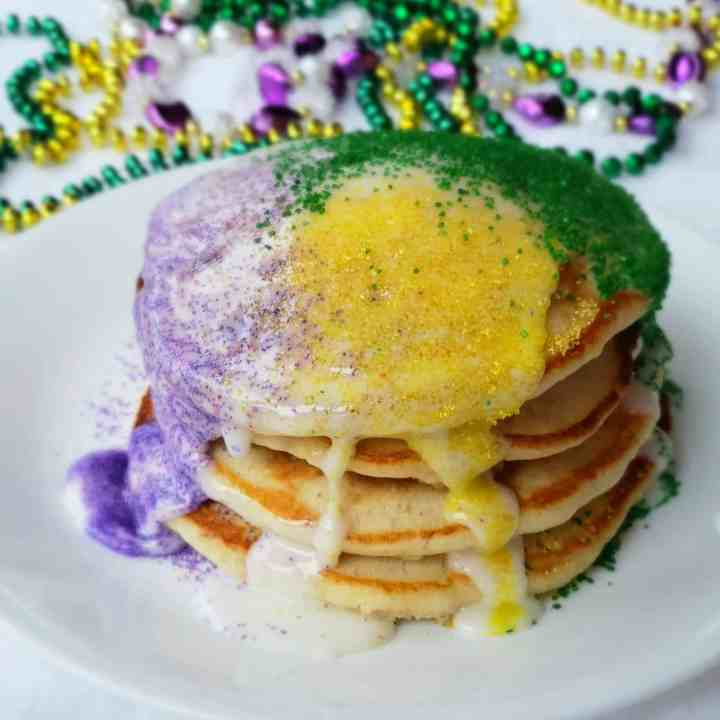 A stack of four pancakes with mardi gras beads in background.Can't make it to Mardi Gras? These shortcut banana pancakes drizzled with icing and sugar sprinkles are perfect for Fat Tuesday- also called Pancake Day!
