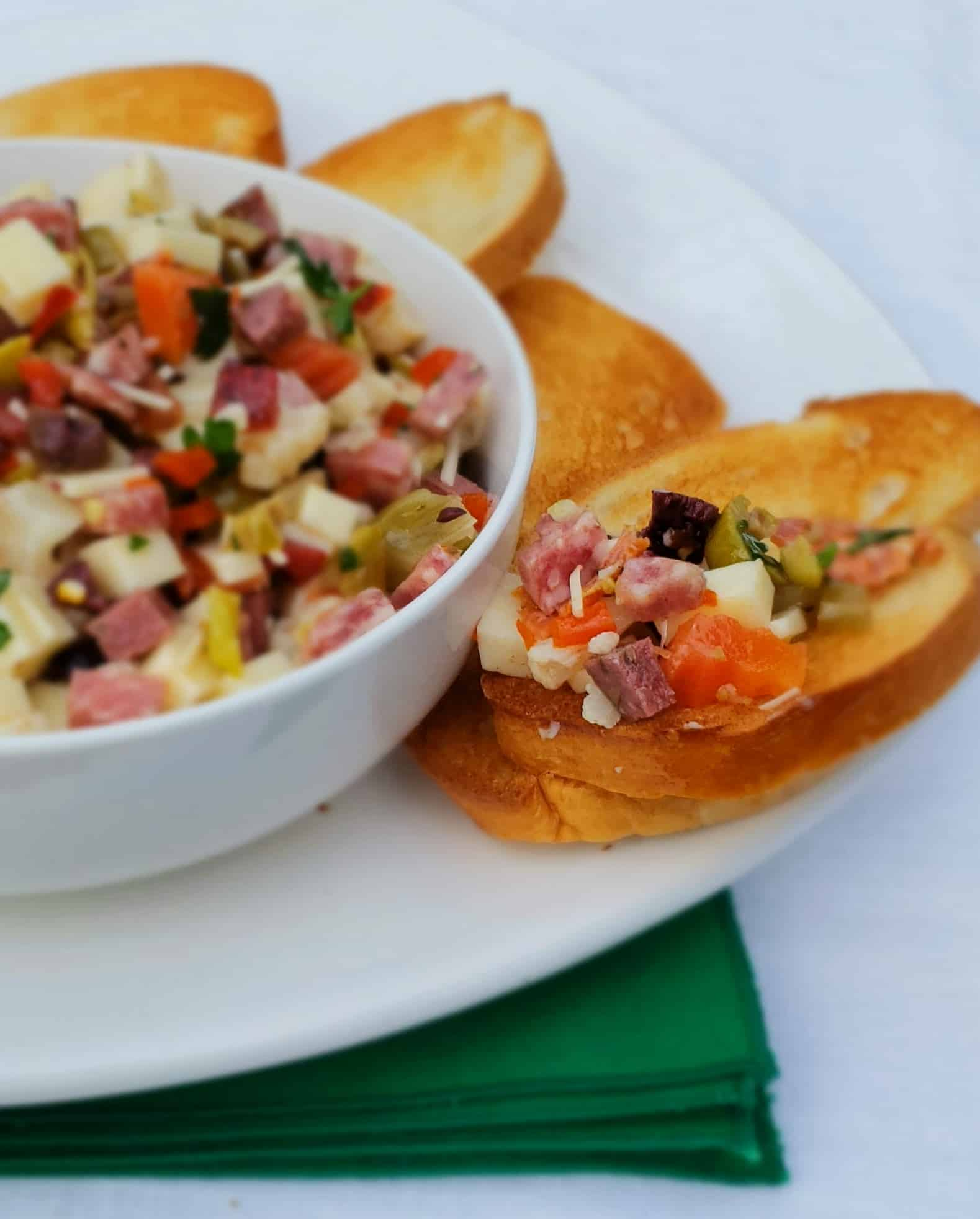 Muffaletta Dip is perfect served with French bread crostini for any occasion not just Mardi Gras or Fat Tuesday
