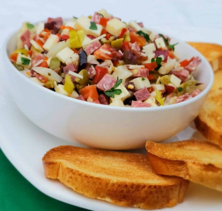 muffaletta dip in white bowl with toasted baguette slices