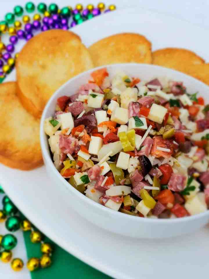 Muffaletta Dip for Mardi Gras and Fat Tuesday or any day you are craving a little NOLA flavor.. Served with French Bread crostini . Beads in the background