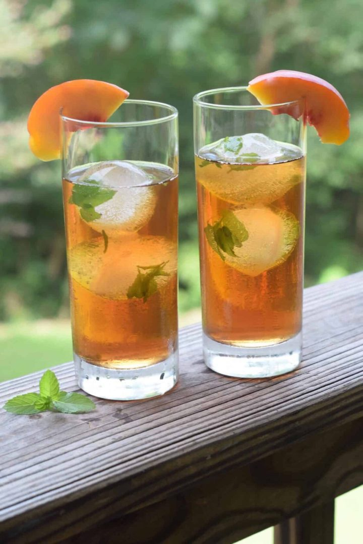 Mint Ice cubes in tall tea glasses with peach wedges on glass. Glasses on wooden railing with greenery in background