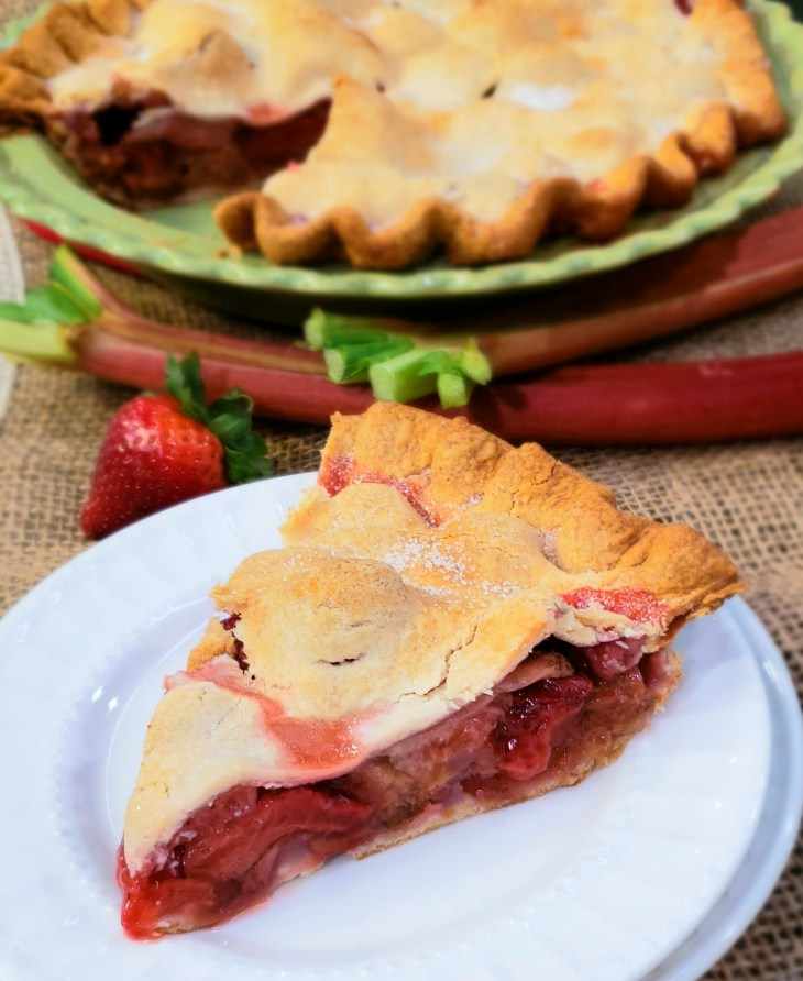 Shortcut Strawberry Rhubarb Pie. The shortcut is using refrigerated, rolled up pie crust. A fresh strawberry and fresh rhubarb stalks in background.