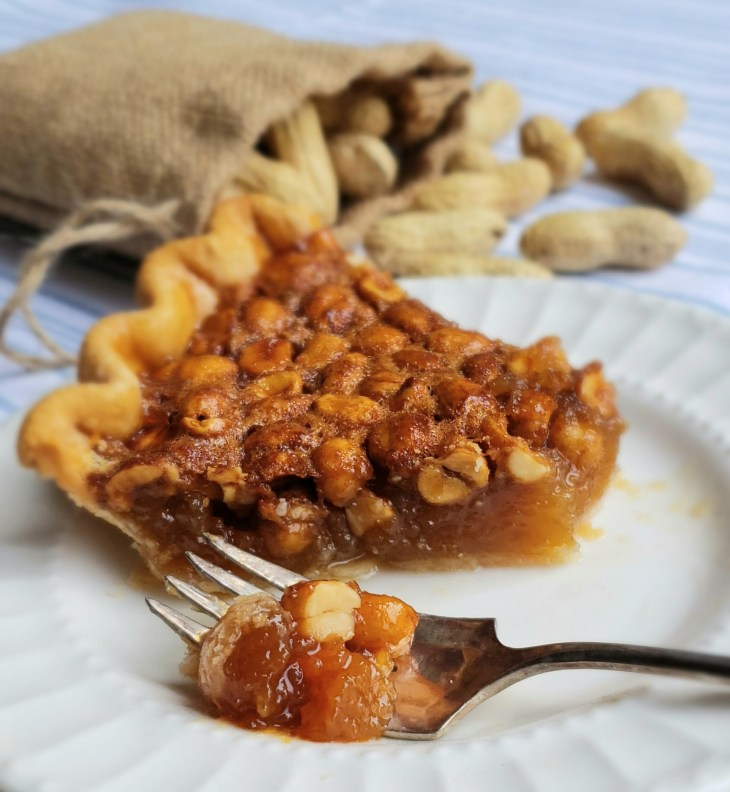 peanut pie with bite cut off on fork on white plate peanuts in a bag