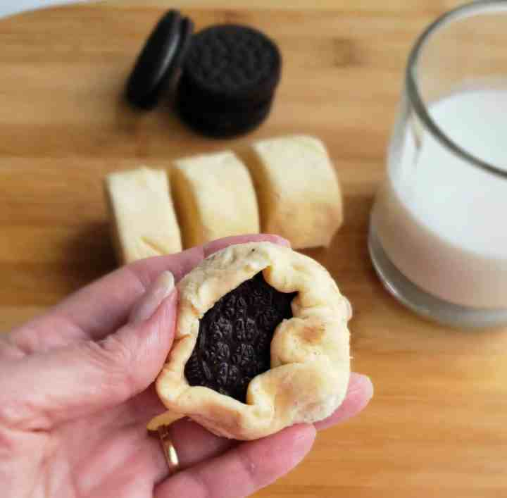 crescent roll dough wrapped around a chocolate cookie with stack of cookies and cup of milk in background