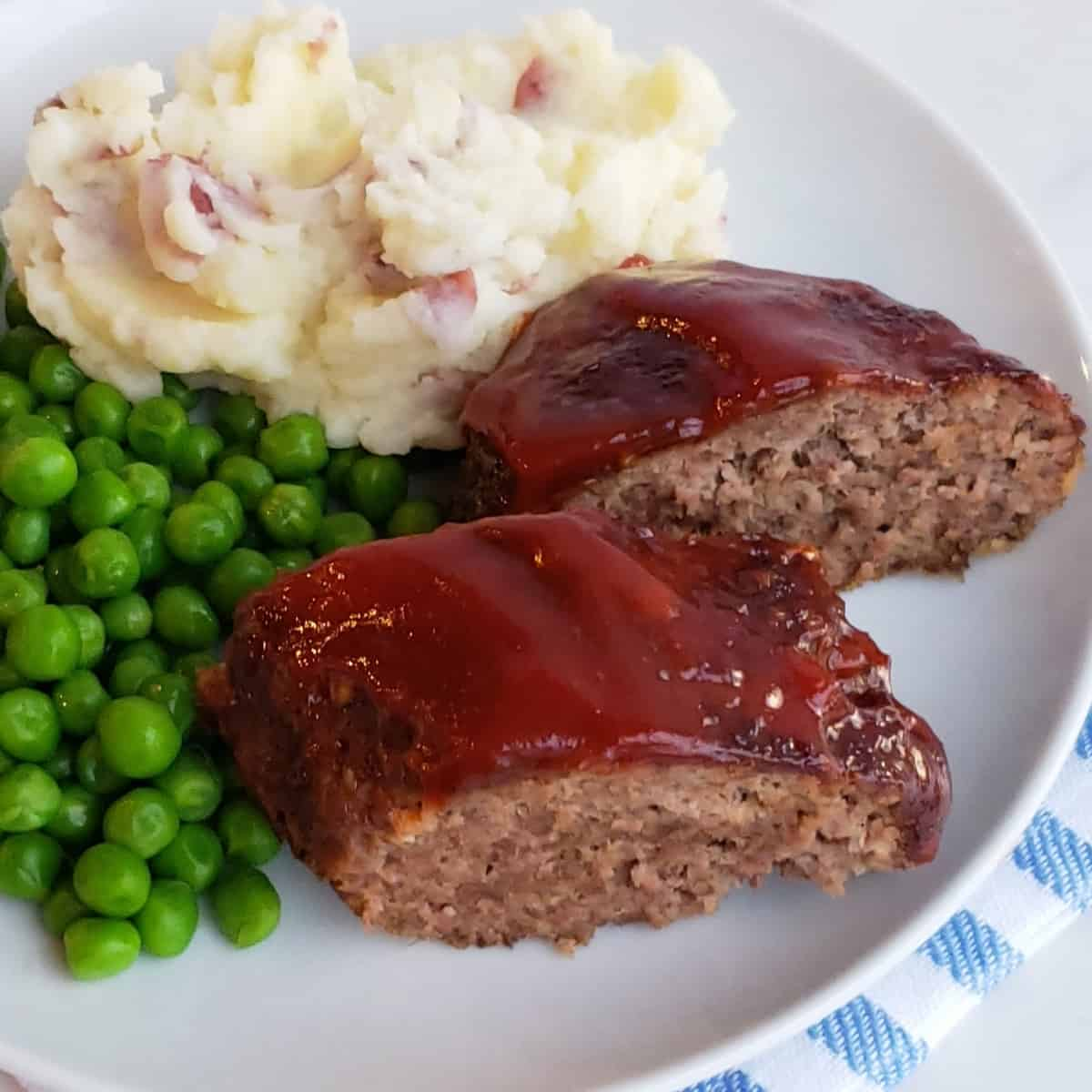 Sliced meatloaf with ketchup sauce on top served on a plate of mashed potatoes and English peas