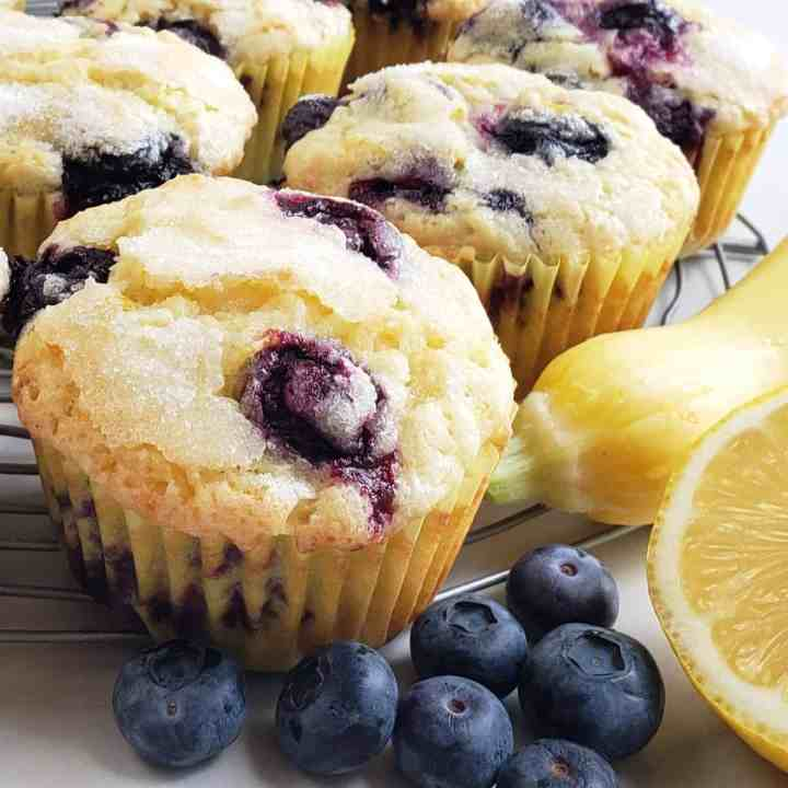 blueberry muffins with blueberries, yellow squash and cut lemon on surface