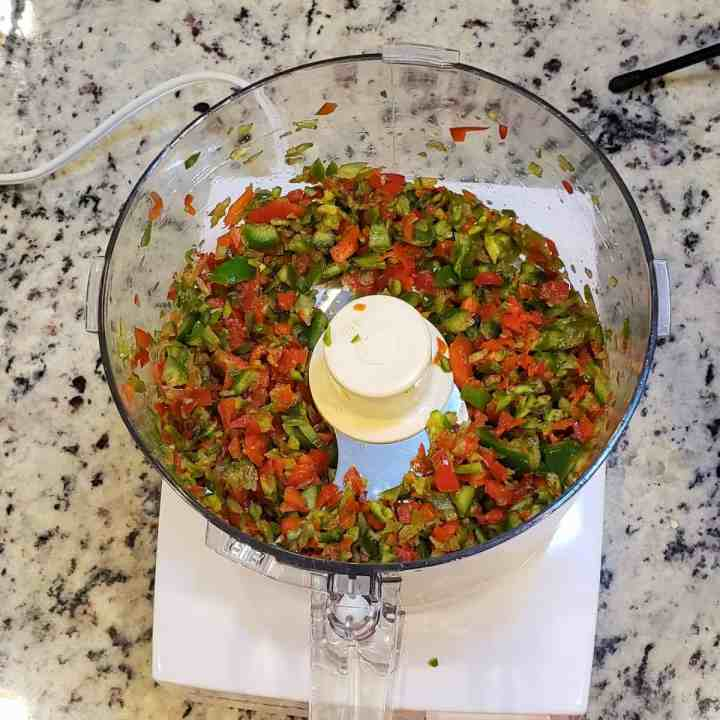 Minced jalapeno and red pepper minced in a food processor; top view