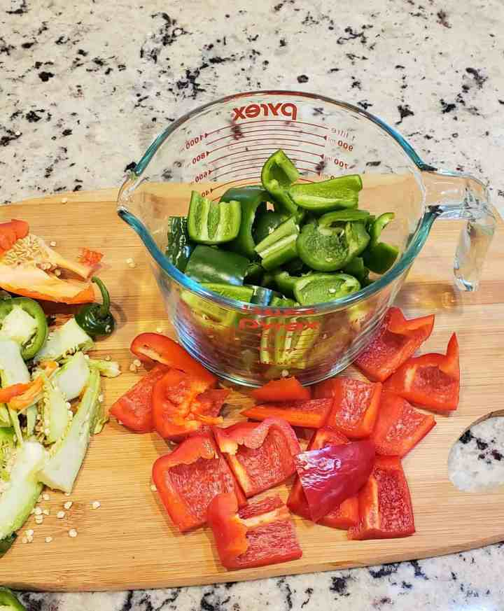 Measuring cup of 1-inch pieces jalapeno peppers; 1 -inch pieces red bell pepper on wooden cutting board