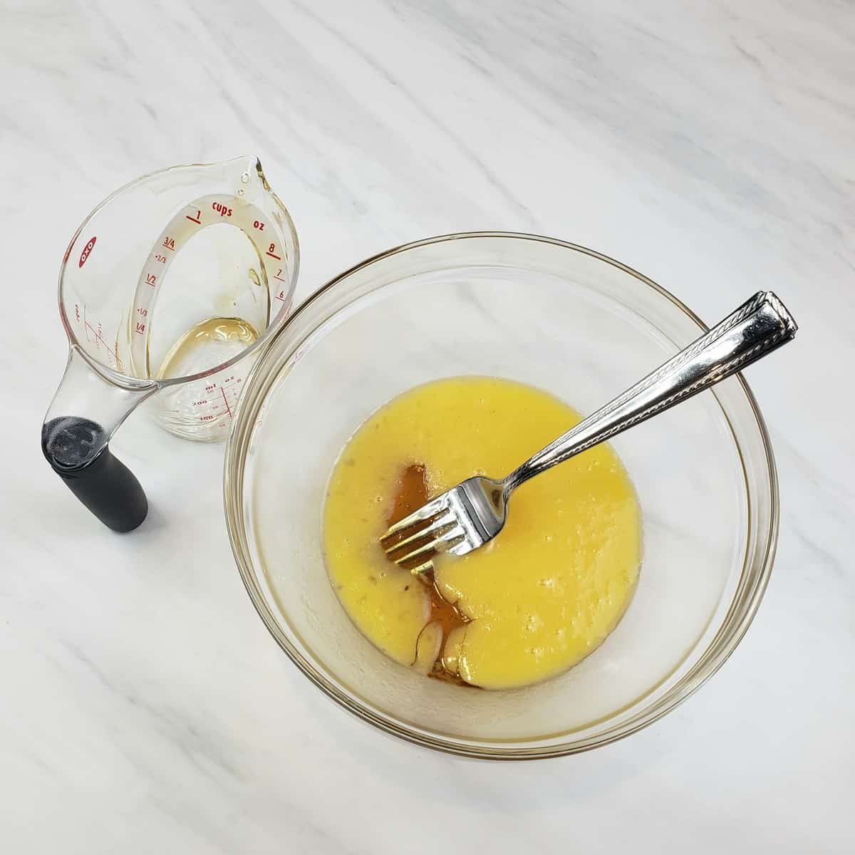 Melted butter and honey in a glass bowl with a fork