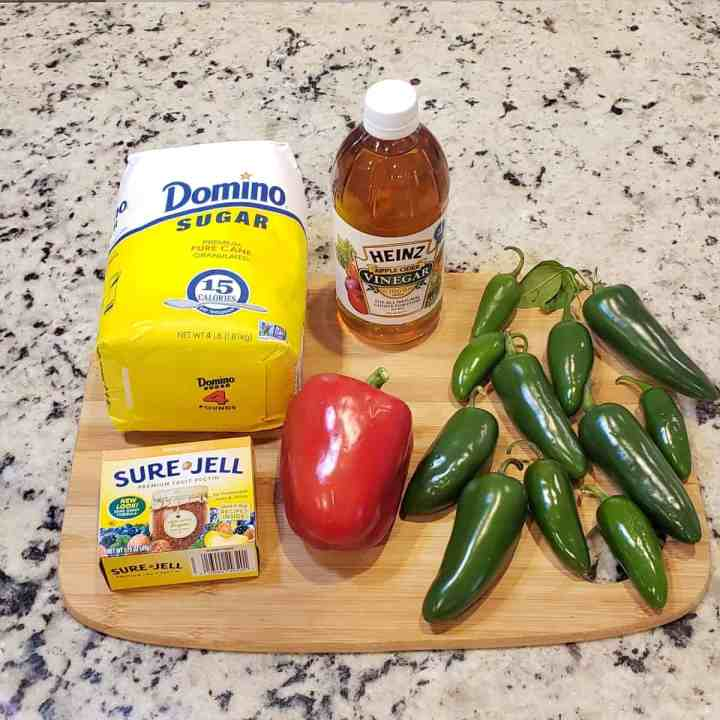 Ingredients for pepper jelly on a wooden cutting board: sugar, Sure-Jell, apple cider vinegar, red pepper, jalapeno peppers