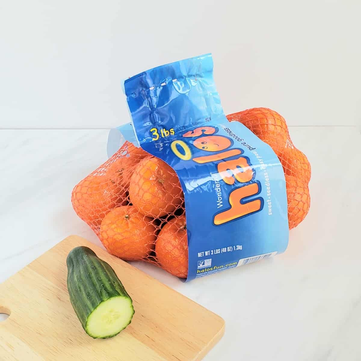 Bag of mandarin oranges and a pied of cucumber on a wooden cutting board
