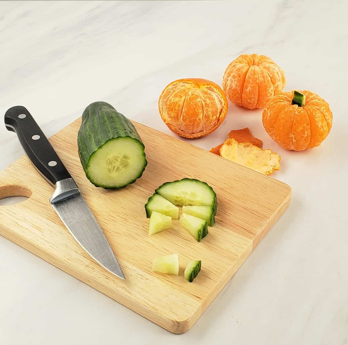 Mandarin oranges; some peeled. knife and sliced cucumber on wooden cutting board