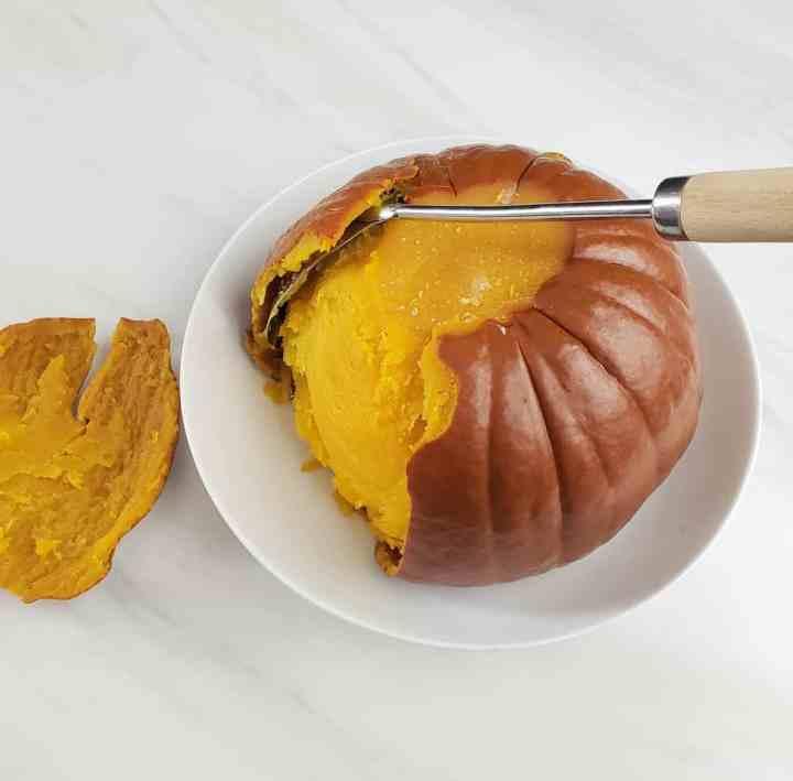 metal spoon pushing back cooked pumpkin peel