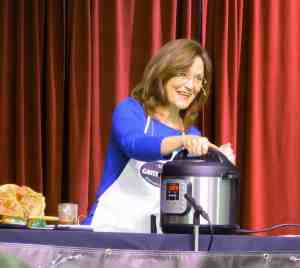 woman behind Instant Pot with red curtains behind her