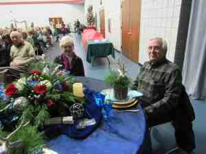 man and woman sitting at round table decorated for Christmas