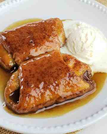 Pumpkin Spice Dumplings in sauce on a white plate served with vanilla ice cream
