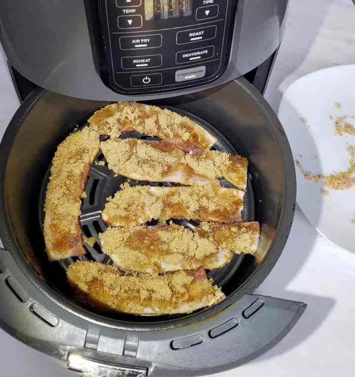 bacon topped with brown sugar in an air fryer basket