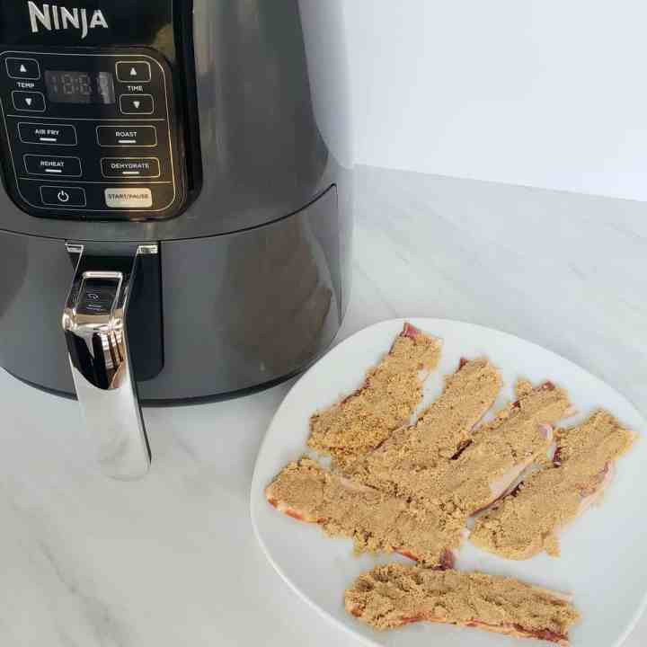 air fryer with plate of bacon topped with brown sugar