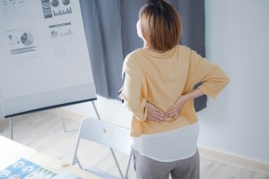 Woman with back pain in office