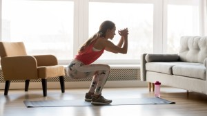 woman working out on yoga mat in her living room