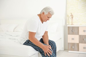 mature man experiencing knee pain at home