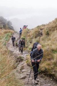 Manouk wandelt op een pad van de Inca Trail met haar backpack tussen het hoge gras
