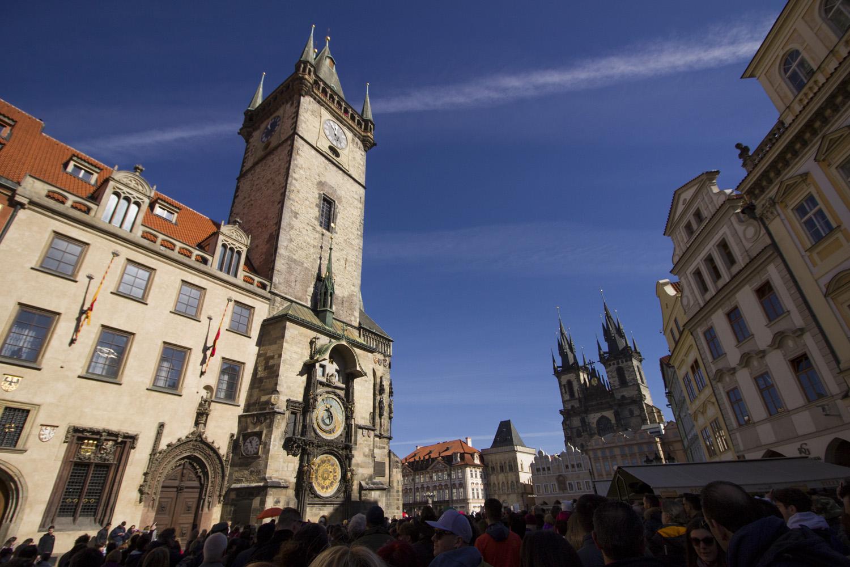 Wat te doen in Praag: de astronomische klok op de toren op het centrale plein van Praag met een groep mensen ervoor.