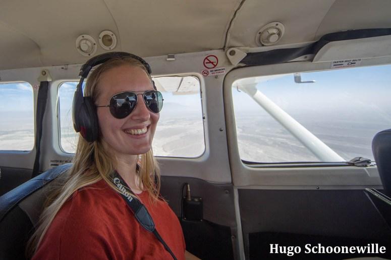 Manouk aan het raam in het vliegtuig over de Nazcalijnen met een koptelefoon op.