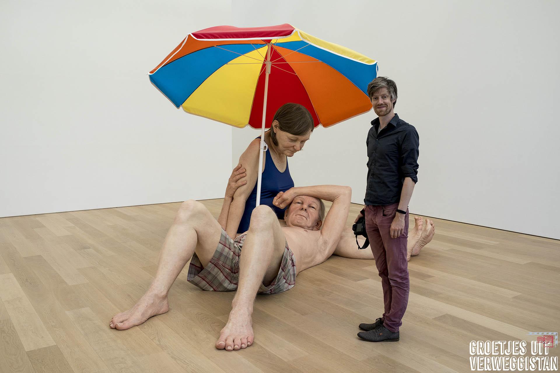 Twee realistische beelden van een ouder echtpaar onder een parasol: twee keer zo groot als normale mensen. Kunstwerk van Ron Mueck.