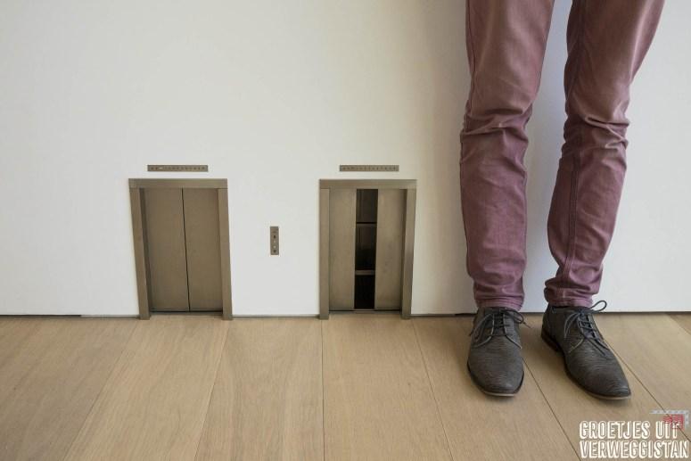 Kunstwerk van Maurizio Cattelan: twee kleine liften op enkelhoogte waarvan de deuren open en dicht gaan alsof ze echt werken.
