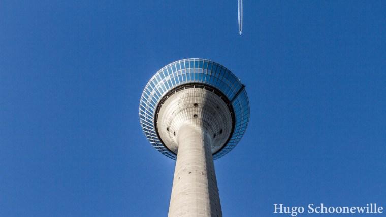 De Rheinturm in Düsseldorf van onderaf gezien, met een passerend vliegtuig.