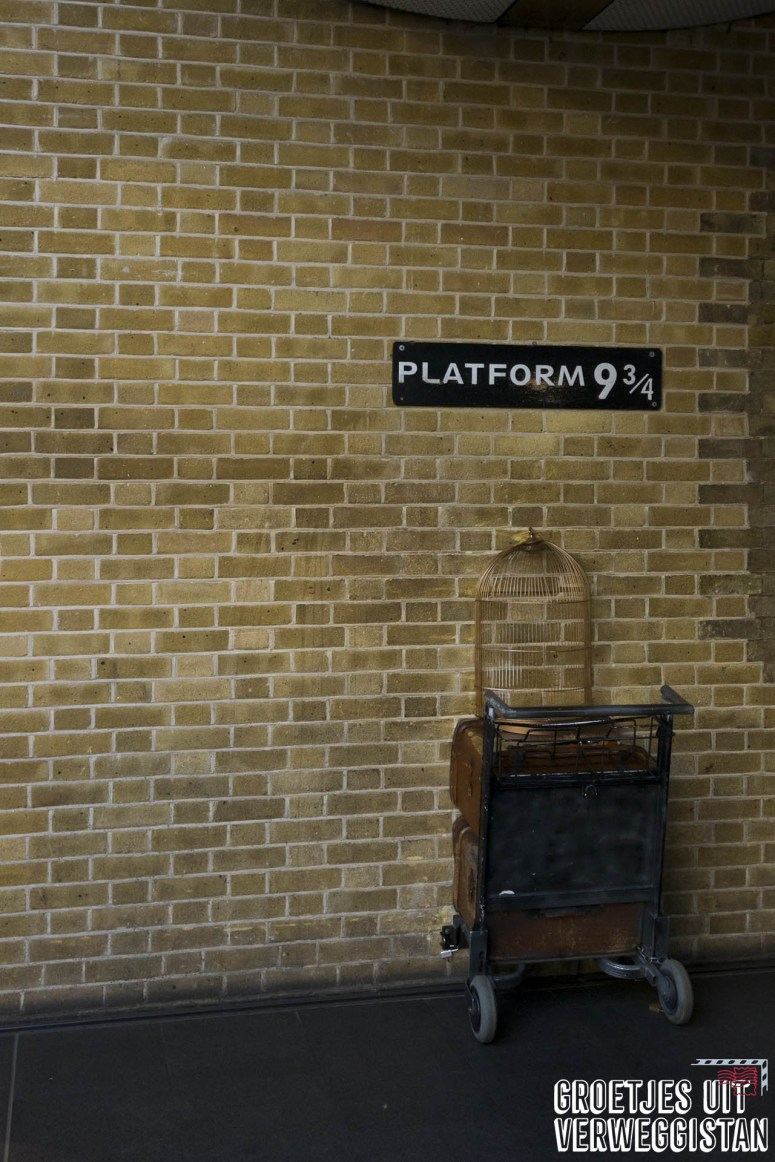 De trolley en muur bij Platform 9 3/4 in King's Cross.