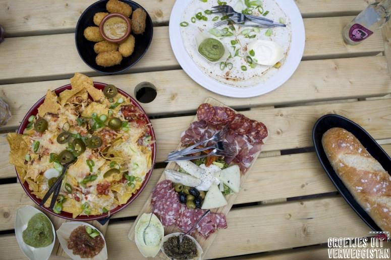 Plateaus met hapje bij De Uurwerker: nacho's, vlees, bitterballen en drankjes.