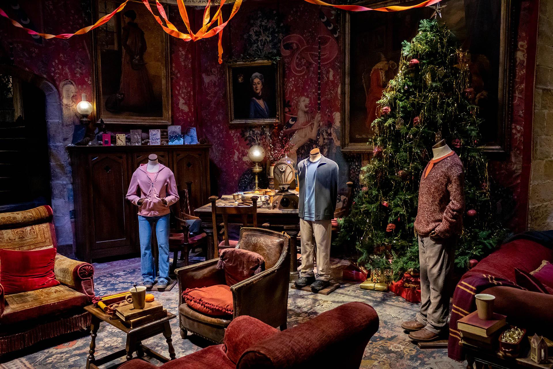 De leerlingenkamer van Gryffindor in kerstsfeer met een kerstboom en poppen met de kleding van Harry Potter, Ron en Hermione in de Studio Tour