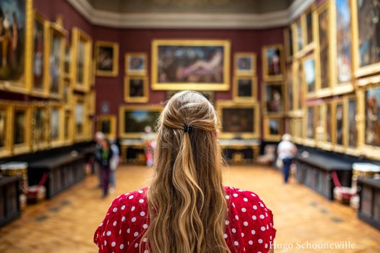 Blond meisje met rood gestipte jurk in de museumzaal van Musee Conde met allerlei schilderijen in gouden lijsten op de achtergrond.