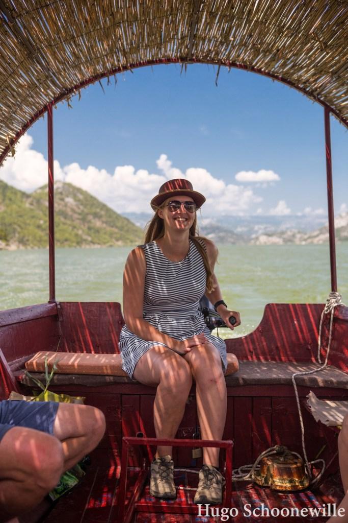 Meisje aan het roer van een houten boot met rieten dak op het Skadarmeer in Montenegro.