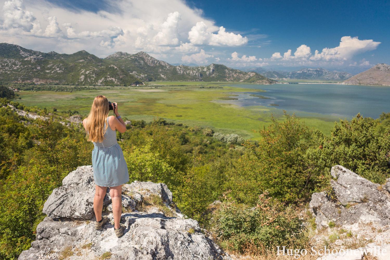 Meisje kijkt vanaf rots uit over het Skadarmeer in Montenegro met een fotocamera.