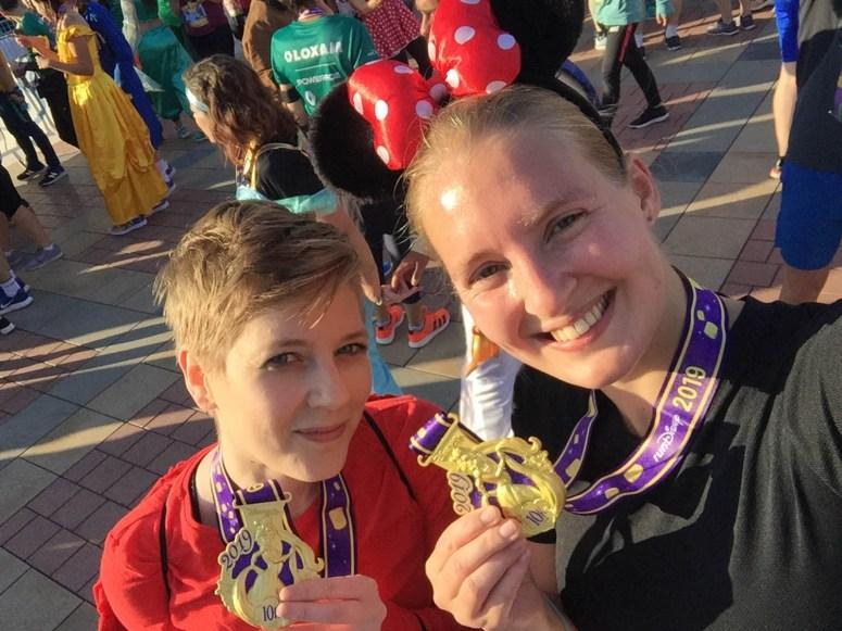 Finishfoto met twee medailles met Rapunzel na de 10 kilometer door Disney.