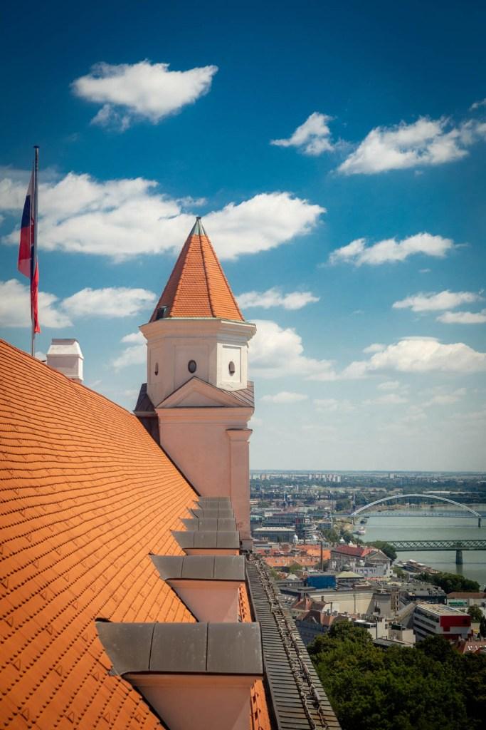 De torens en het dak van het kasteel van Bratislava met een blauwe lucht