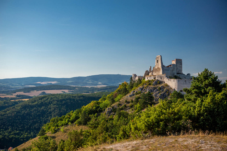 De ruïne van kasteel Čachtice hoog op een heuvel in Slowakije tijdens het gouden uur.