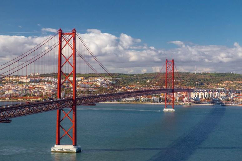 Rode brug in Lissabon over de rivier met Lissabon op de achtergrond.