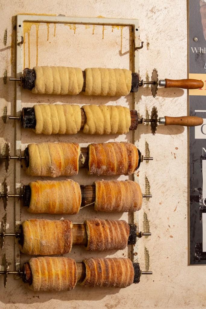 Trdelnik in bakfases op rollen aan de muur van een bakkerij.